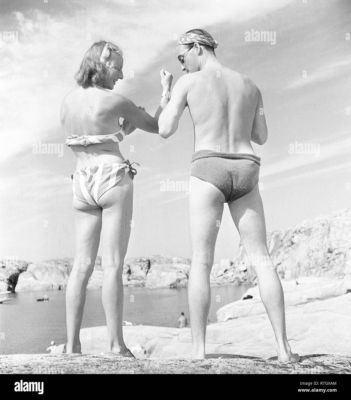 On the beach in the 1940s. A couple is photographed from behind and they look as if they are comparing their arm muscles. She is wearing a bikini and he's wearing a pair of bathing shorts, both equally bad looking in both fitting and fabric.  Photo Kristoffersson ref AC125-6 Sweden 1947 - Stock Image