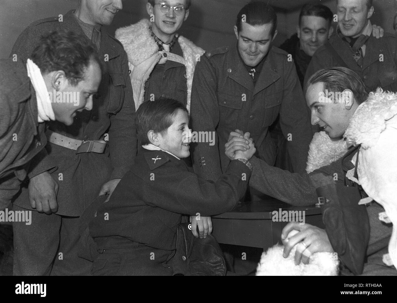 The Winter War. A military conflict between the Soviet union and Finland. It began with a Soviet invasion on november 1939 when Soviet infantery crossed the border on the Karelian Isthmus. About 9500 Swedish volunteer soldiers participated in the war.  Pictured Swedish volunteer soldiers. Nils Knutsson from Stockholm is having an arm-wrestling match with the young Finnish orderly boy Olavi Kukkola. Standing behind them Mårten Elgström who acts as the referee.   January 1940. Photo Kristoffersson ref 103-6. - Stock Image