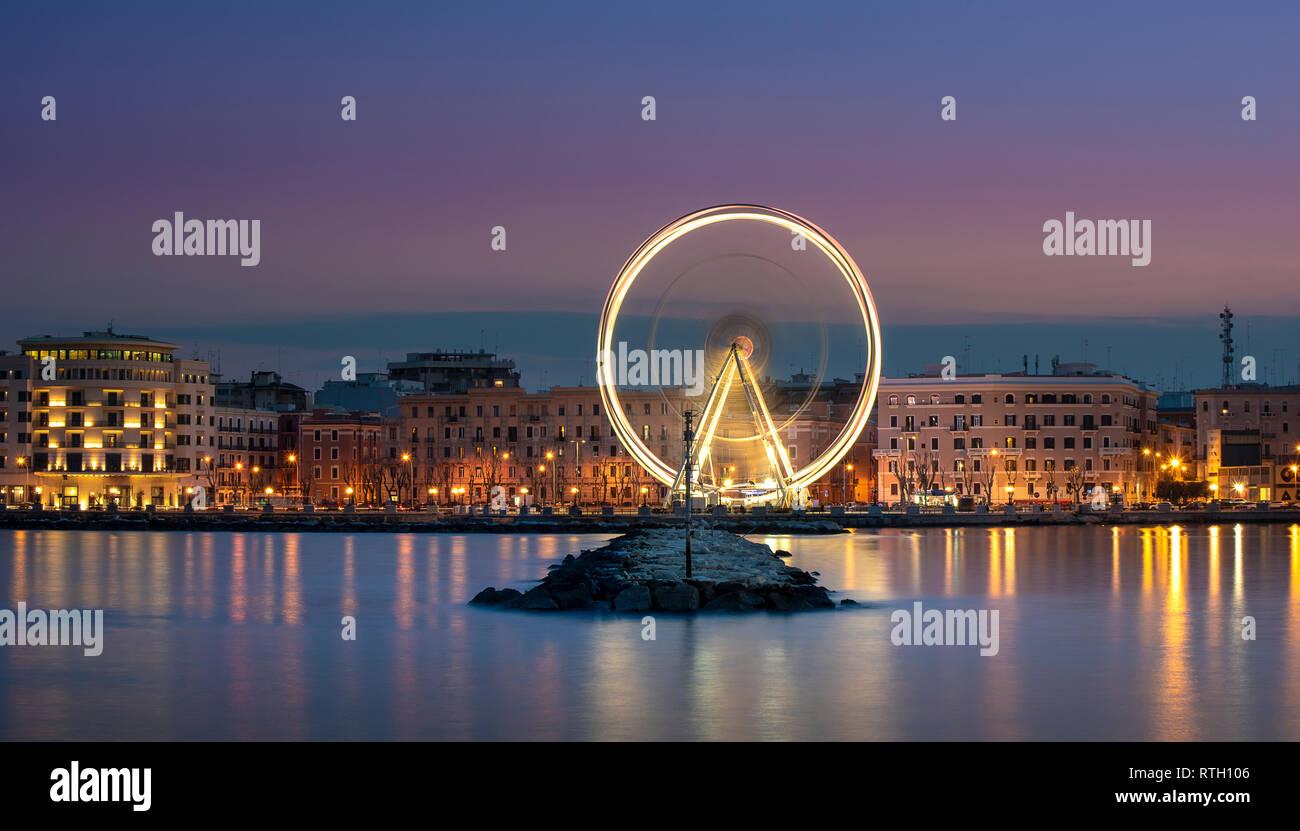Night view of Illuminated giant Ferris wheel on the waterfront of Bari, region of Apulia, Italy. Puglia - Stock Image