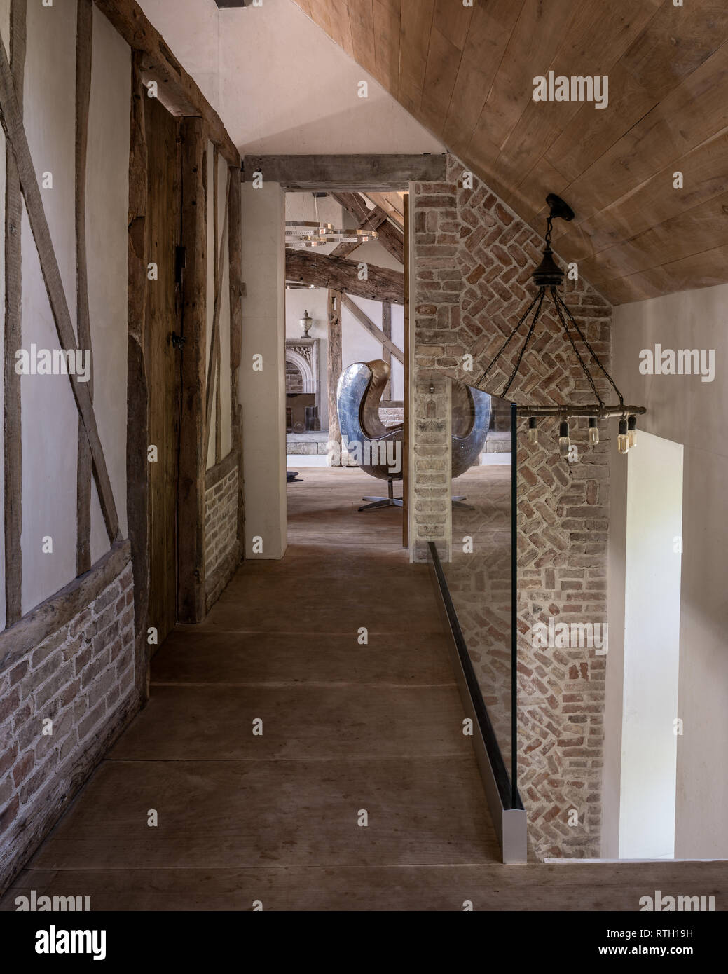 Medieval brickwork  and oak beams  with glass balustrade - Stock Image