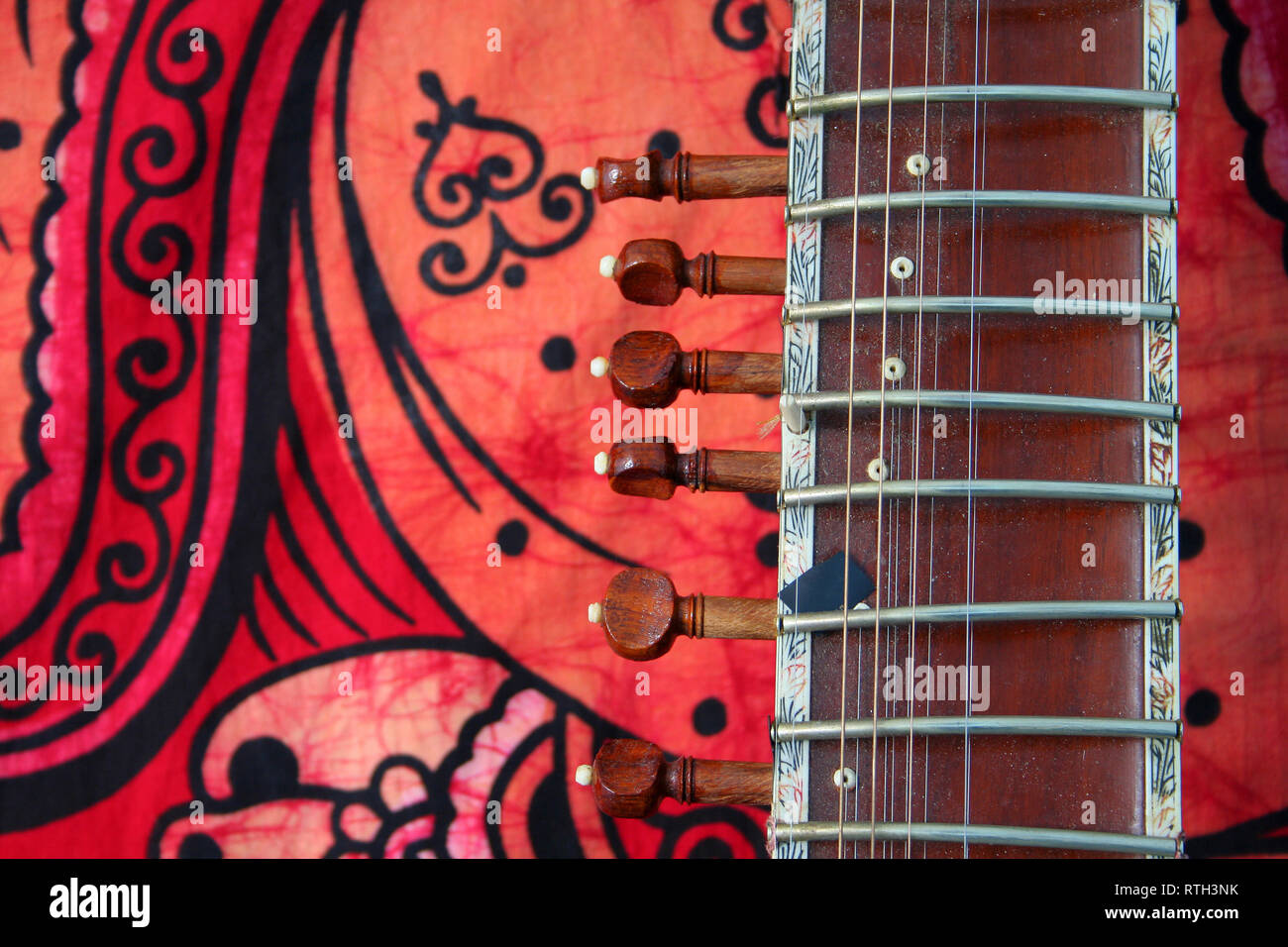 old sitar on red background - ancient indian instrument Stock Photo
