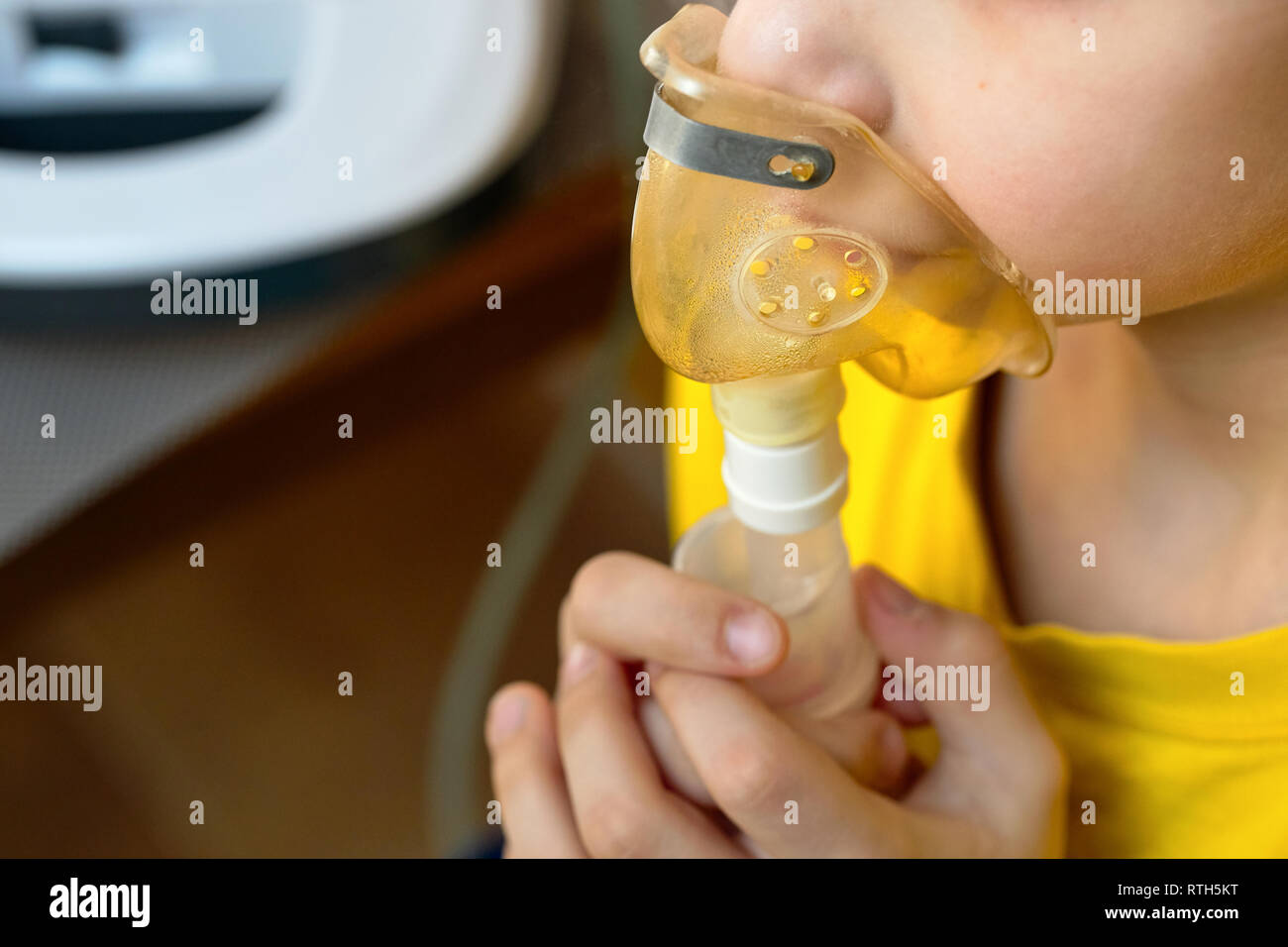 Child makes inhalation at home with nebulizer on out of focus background. Example of combating respiratory diseases such as tracheitis bronchitis pneu - Stock Image