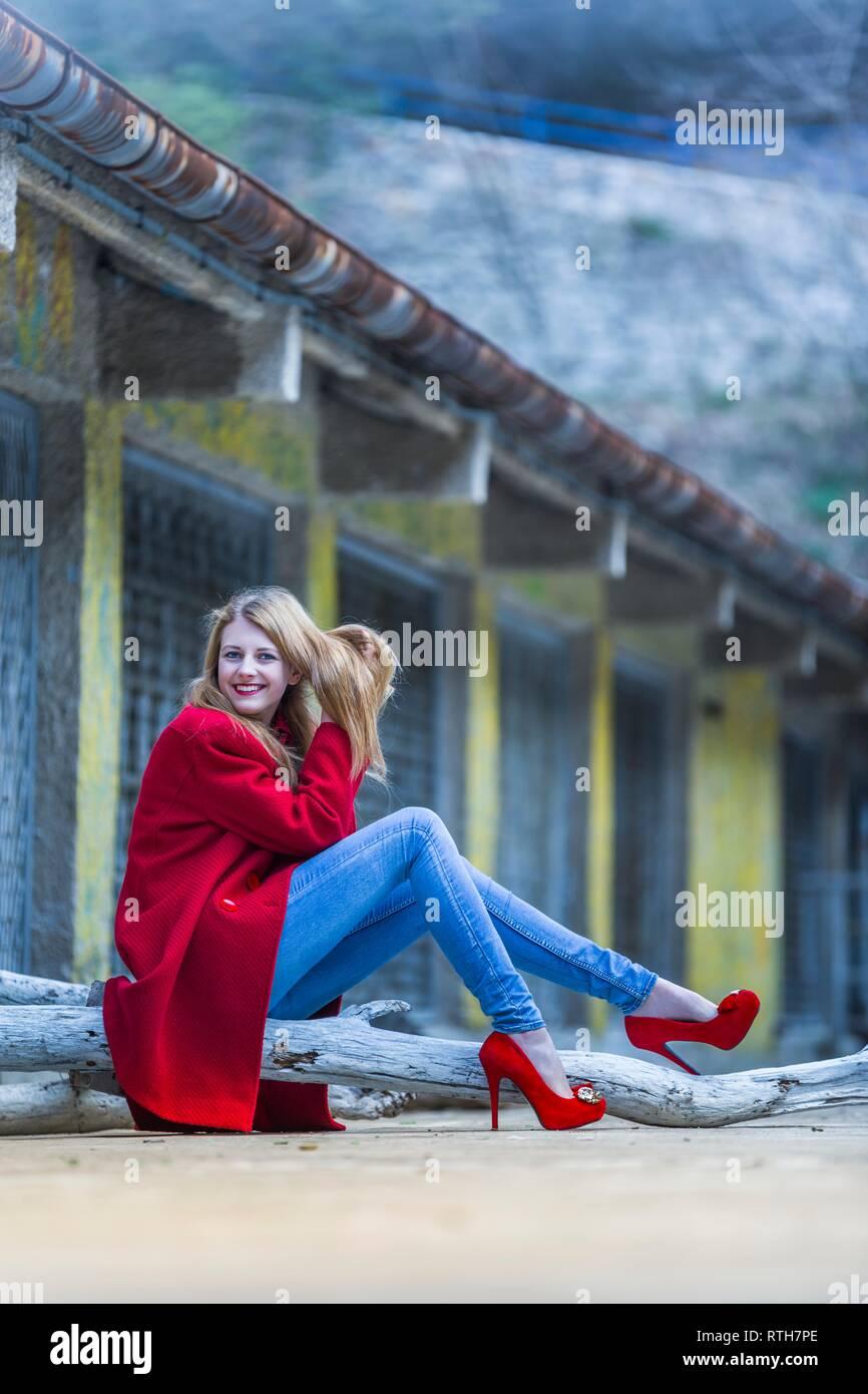 Blonde beautiful teen girl in fancy Red coat is sitting sideways looking smiling at camera legs heels trousers Stock Photo