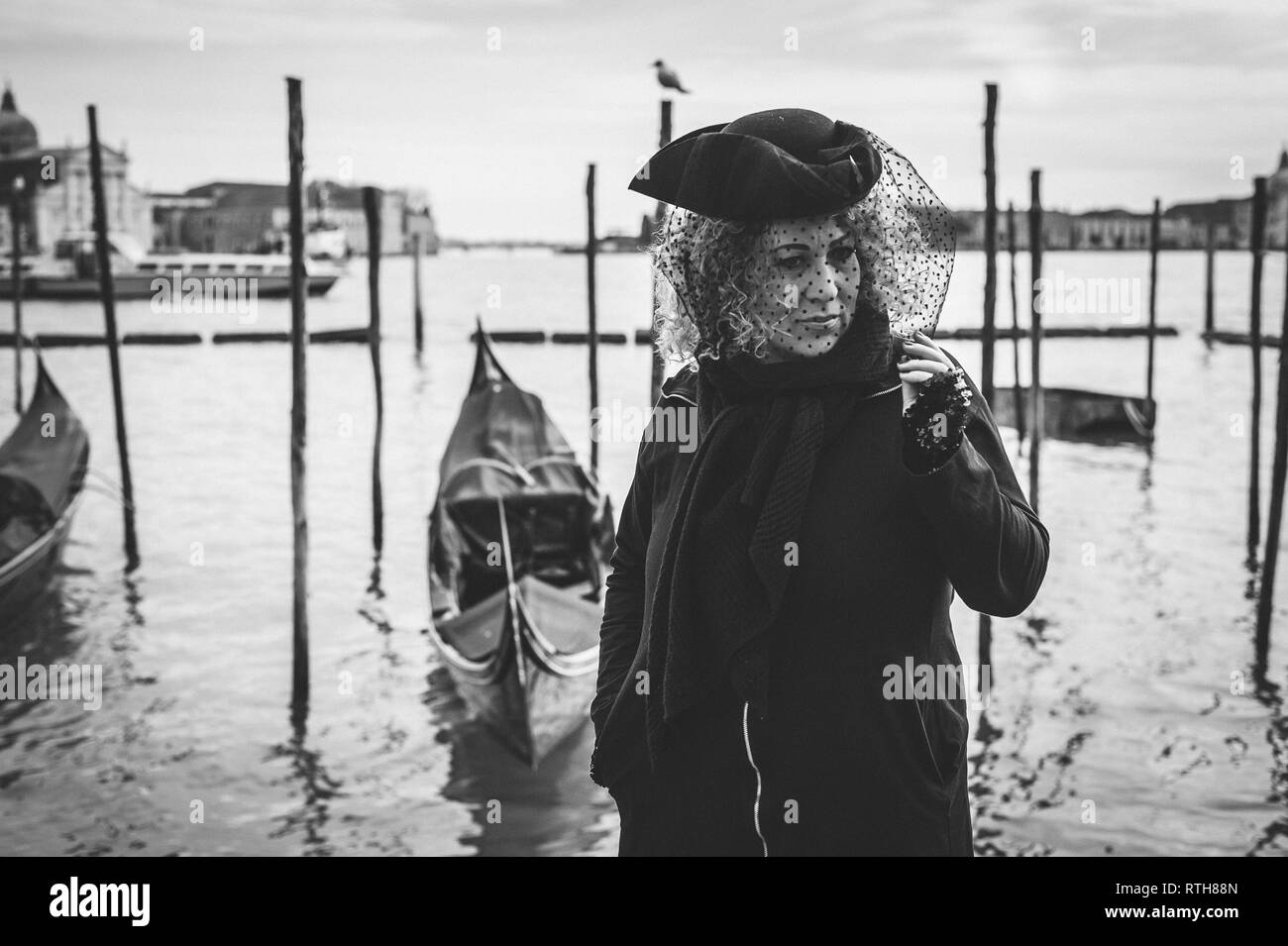 Carnival masked woman standing close to the venetian lagoon in a black and white portrait image - Stock Image