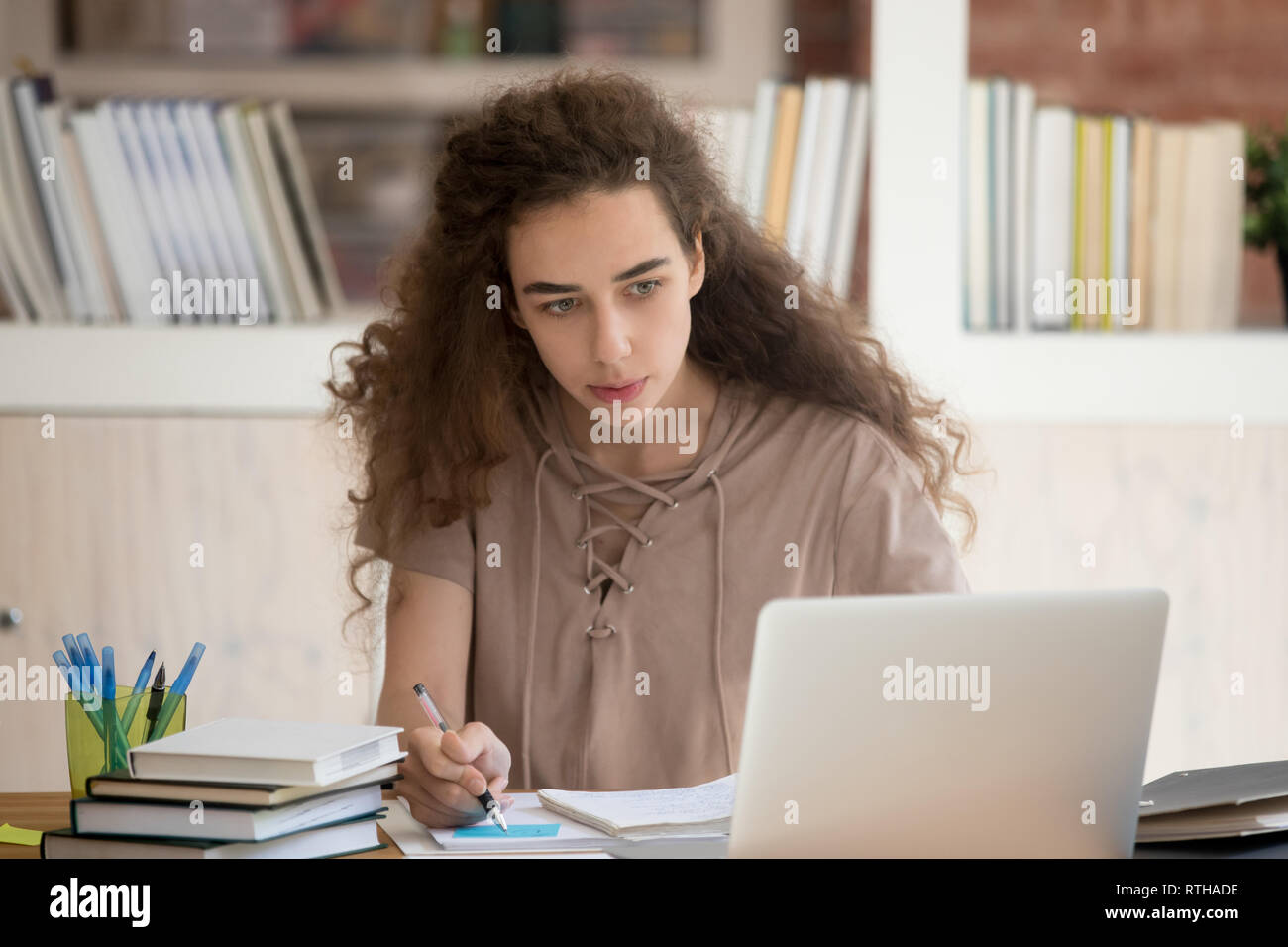 Teen college graduate student studying looking at laptop making notes - Stock Image