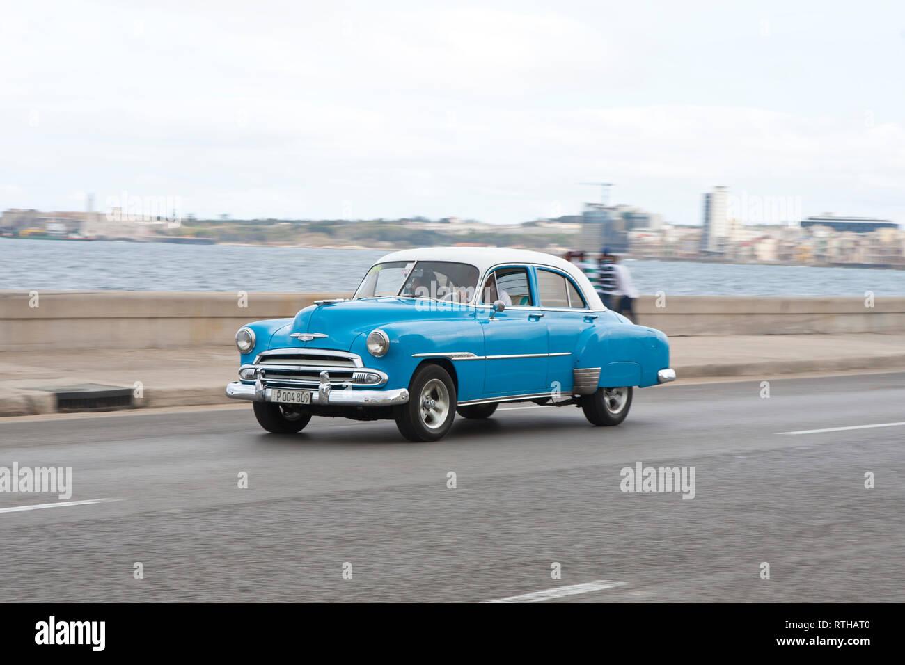 Classic 1950's American car road trip driving along the Malecon in Havana Cuba Stock Photo