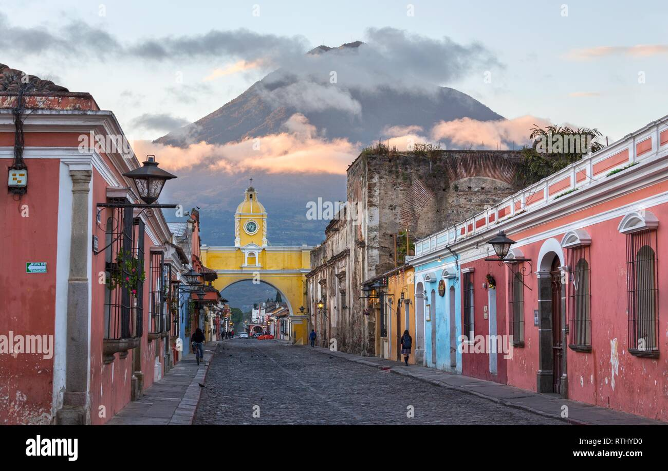 Colonial Architecture and Street Scene during Early Morning Sunrise in Antigua Guatemala with Santa Catalina Arch and Agua Volcano in the Background Stock Photo
