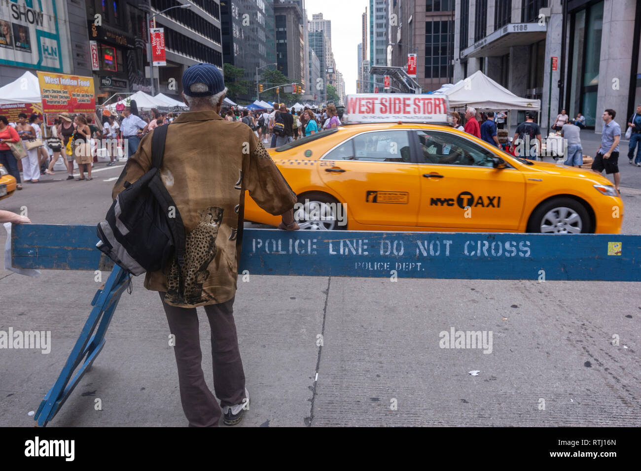 Man in a Police Line Do Not Crossing barrier in 6th Avenue closing to car only for pedestrian with food stands in Manhattan, New York, USA - Stock Image