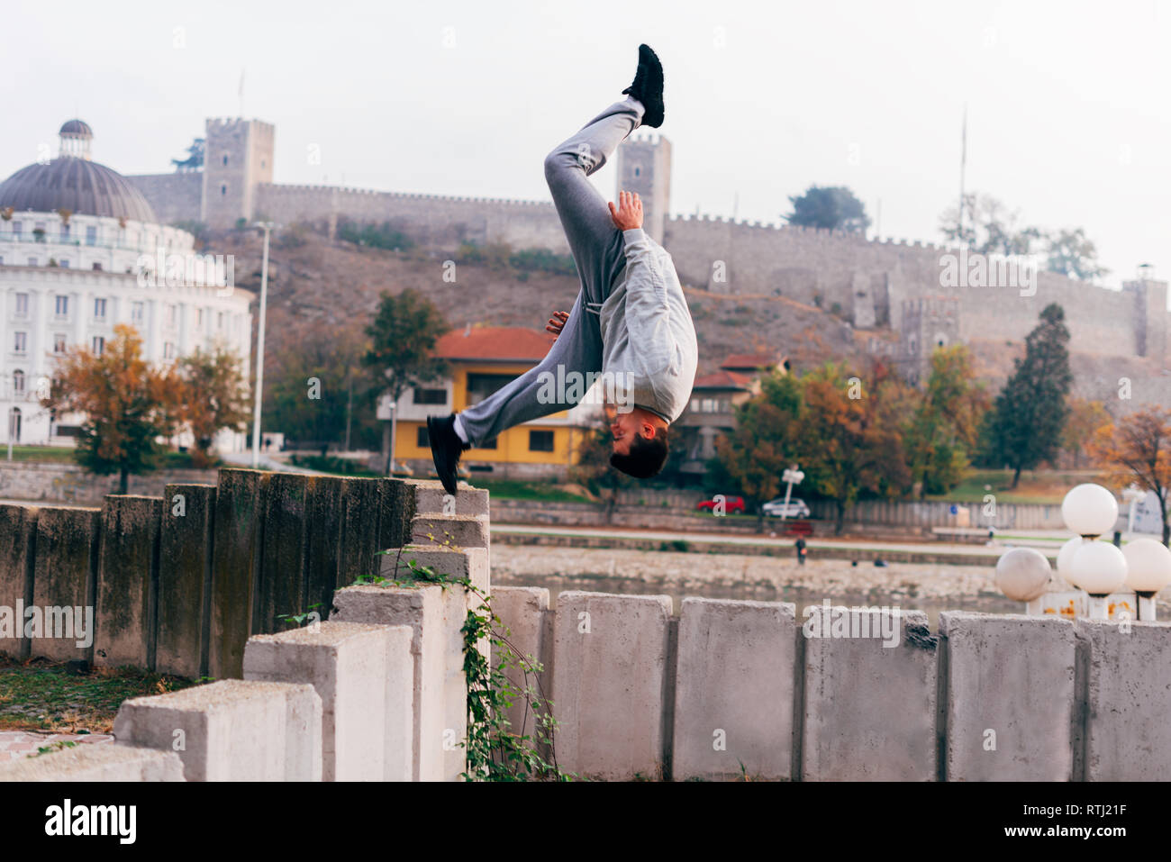 Free runner training parkour jumping on a fence while doing a back flip in the air. - Stock Image