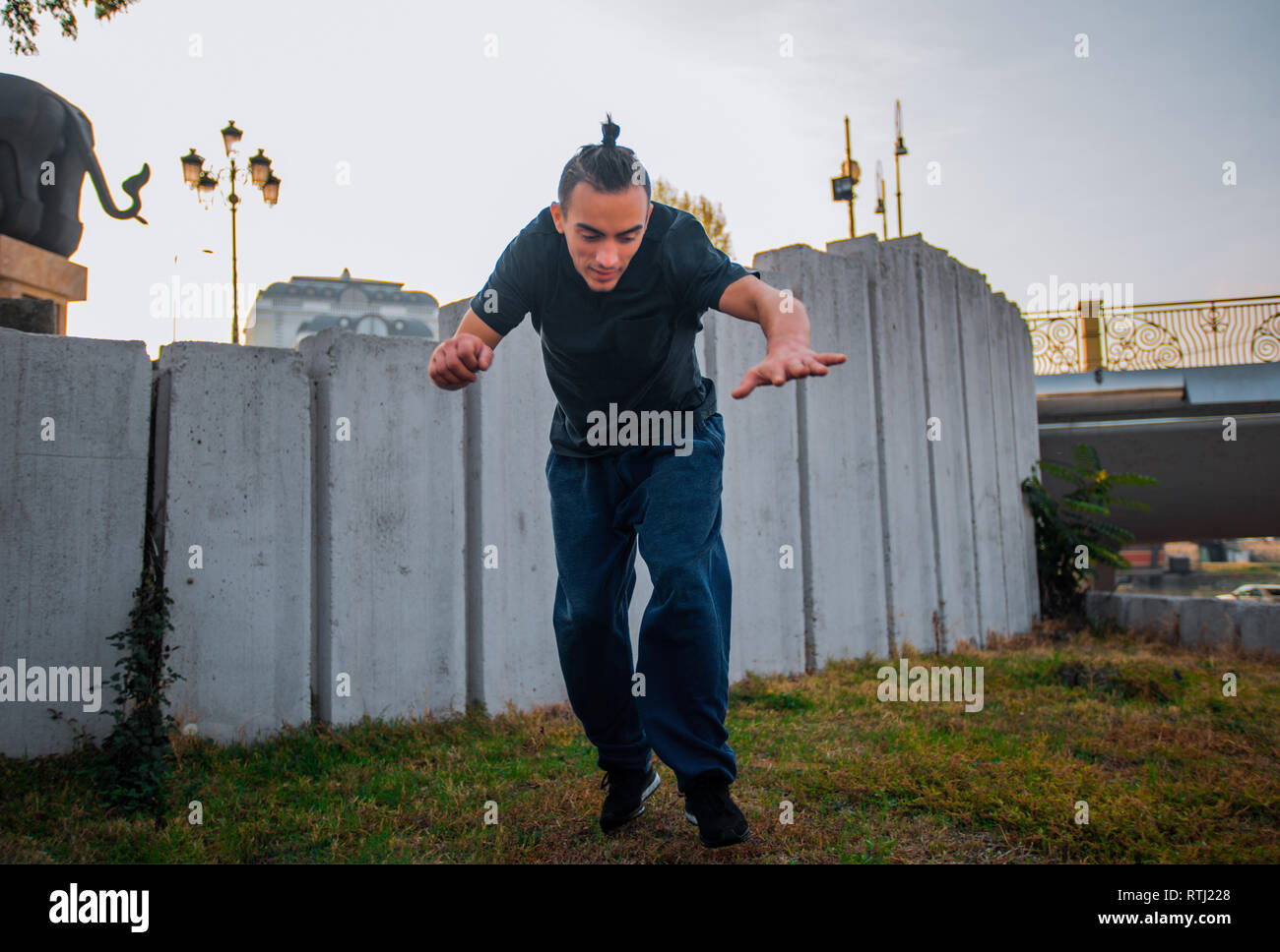 Young roofer doing one handstand while exercise parkour on the top of the building Stock Photo