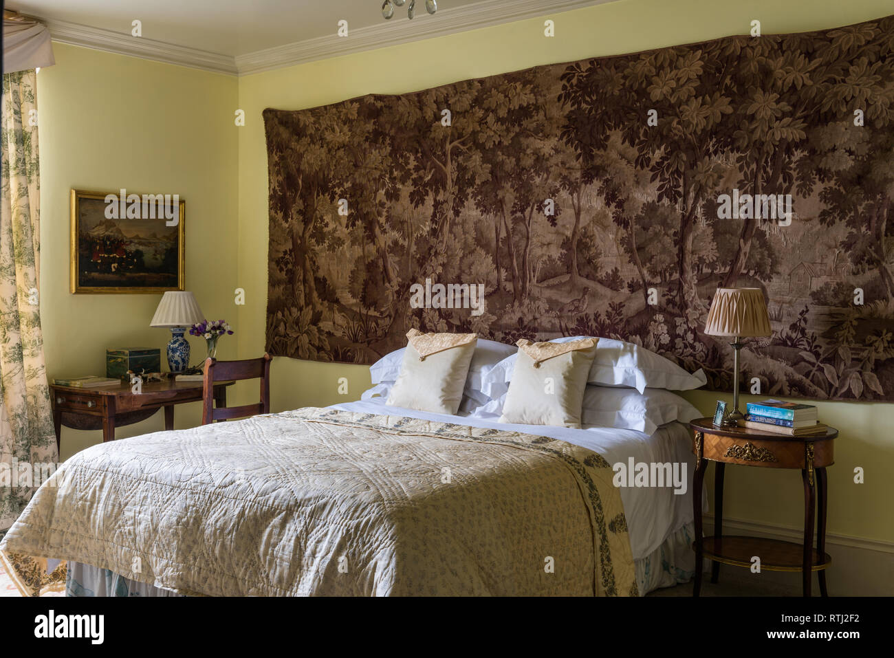 Yellow Quilt On Double Bed With Wall Hanging Of Woodland Scene Stock Photo Alamy