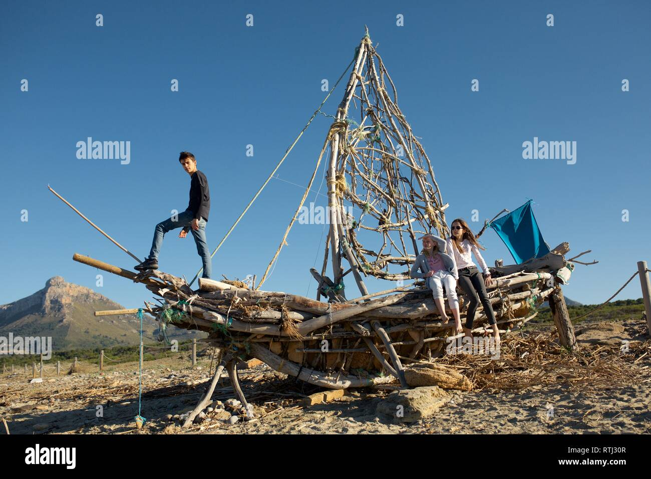 Wild Kids Castaway on Driftwood Ship on the Beach - Stock Image