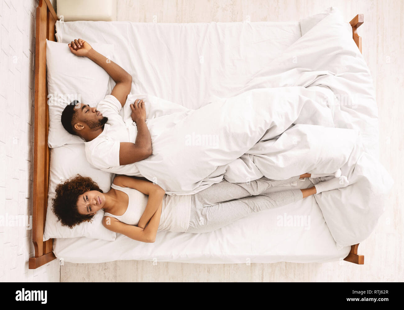 Sad woman lying in bed with sleeping man - Stock Image