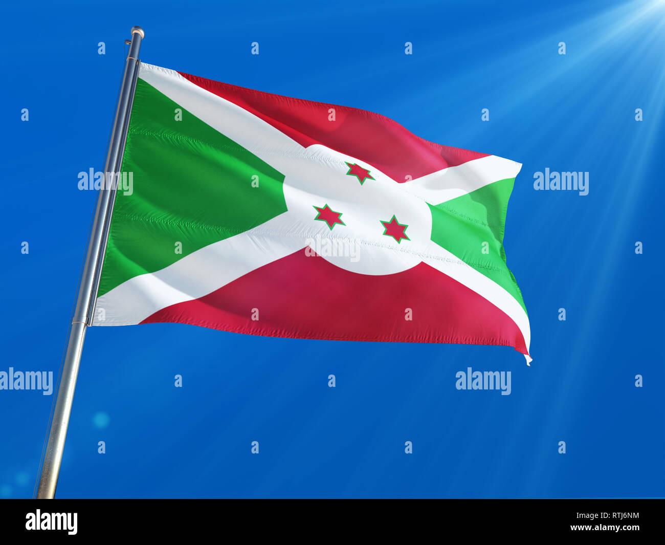 Burundi National Flag Waving on pole against deep blue sky background. High Definition Stock Photo