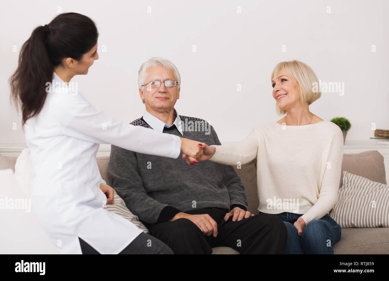 Senior couple welcoming doctor during home visit - Stock Image