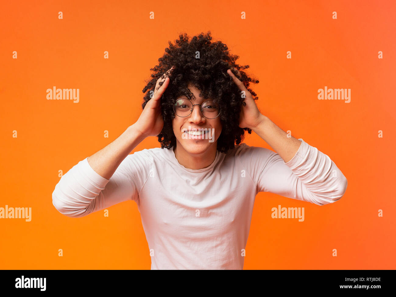 Surprised young curly-haired black guy clutching his head, - Stock Image