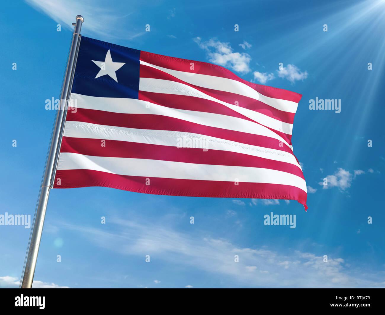 Liberia National Flag Waving on pole against sunny blue sky background. High Definition - Stock Image