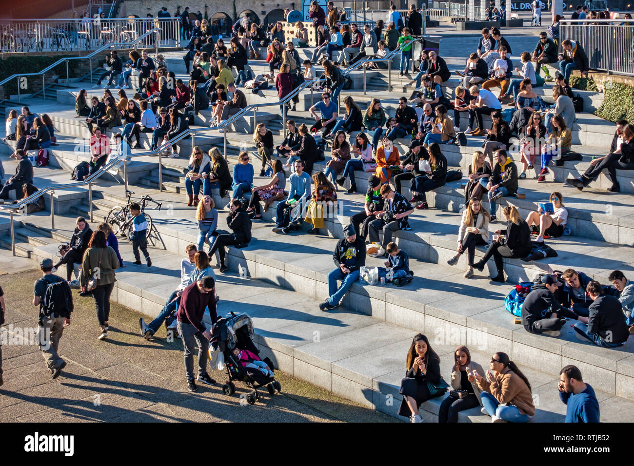 Many people sitting in the sun on steps next to the Regents Canal in front of Coal Drops Yard, Kings Cross, London, England Stock Photo