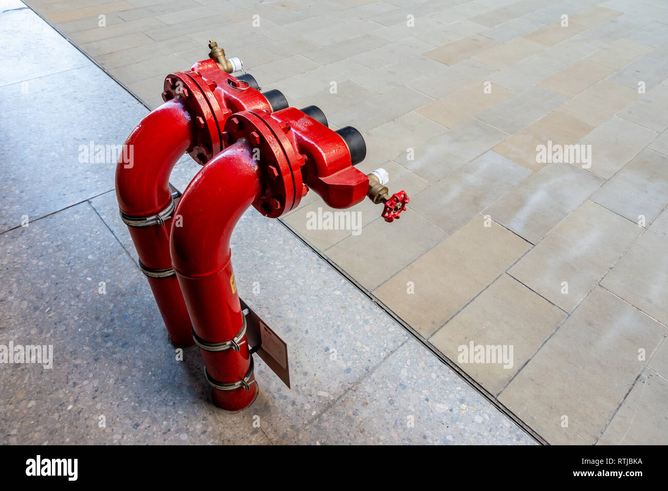2 Contemporary Red Fire Hydrants and Dry Riser outside the Universal Music UK headquarters at Four Pancras Square, Kings Cross, London - Stock Image