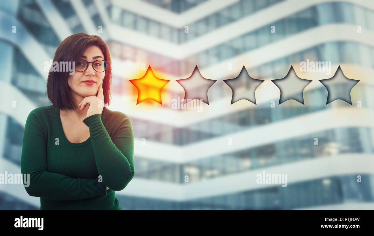 Skeptic young woman holding hand under chin looking disappointed choosing one star rating. Bad and poor customer service concept. Negative feeling, di - Stock Image