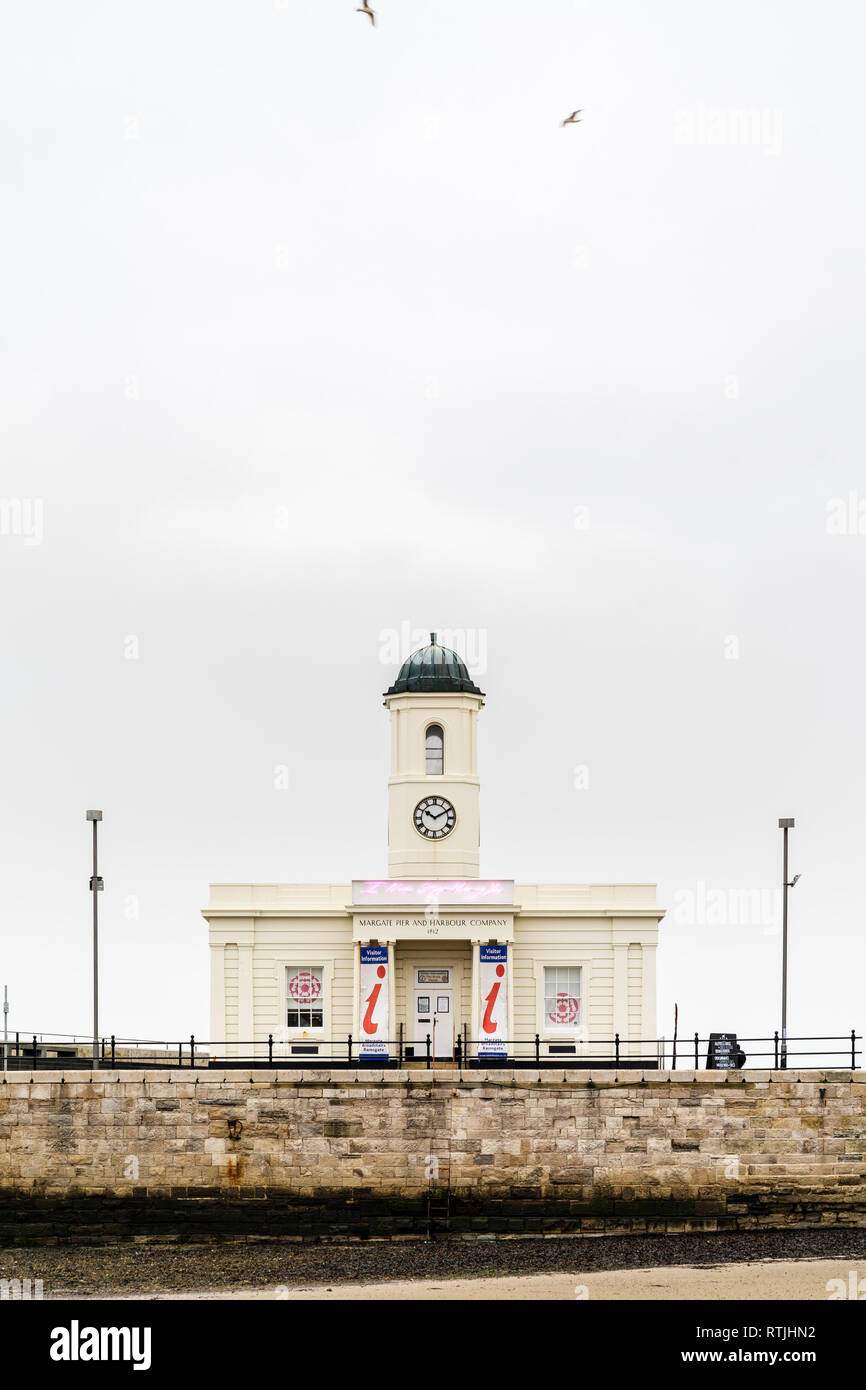 Margate visitor Information Centre, Droit House, double fronted building with clock tower on the stone pier. Overcast grey sky. - Stock Image