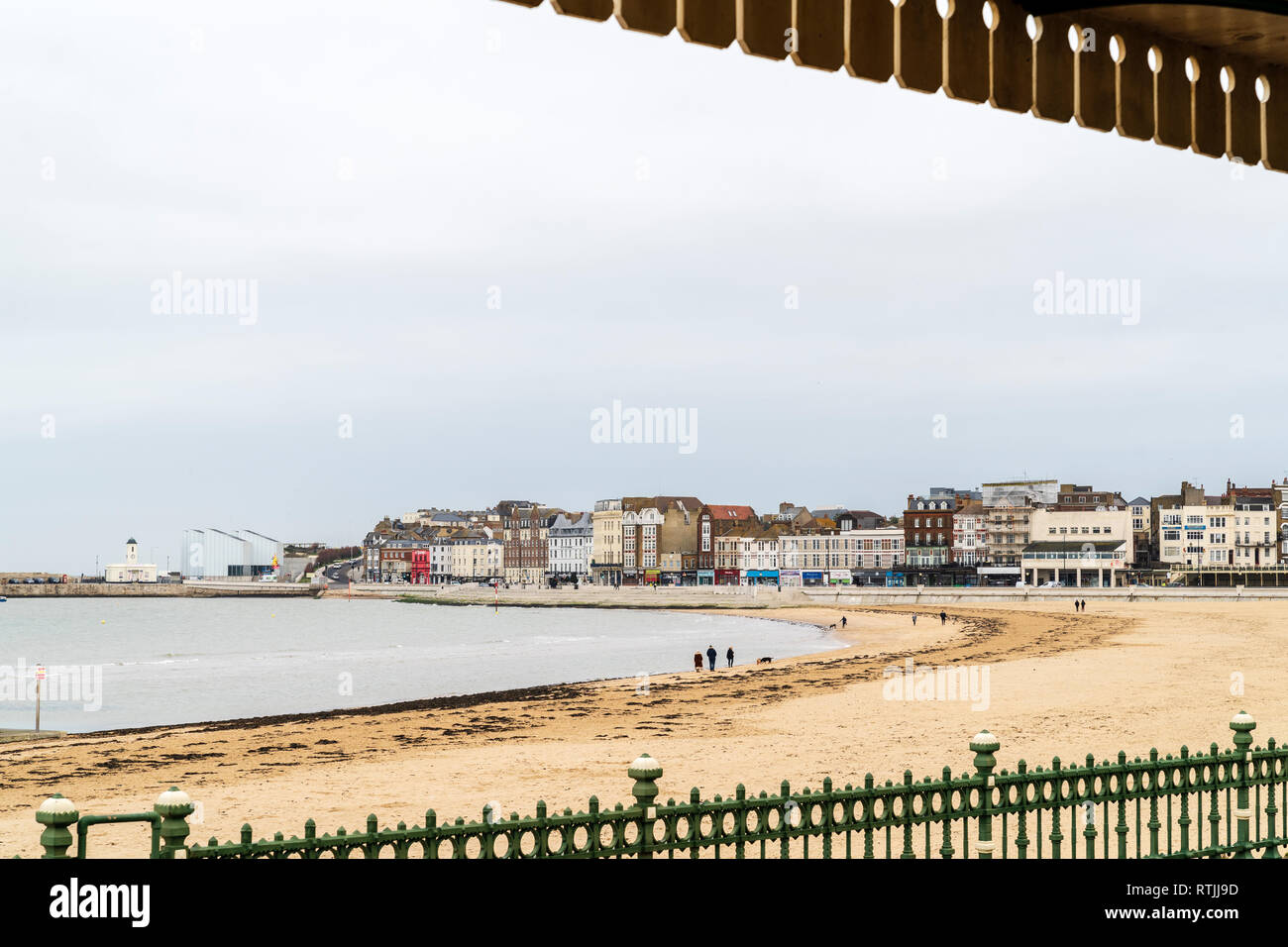 Landscape of Margate seafront with the main sands, Turner Center art gallery and seafront buildings. Grey overcast sky. Some people on beach walking. - Stock Image