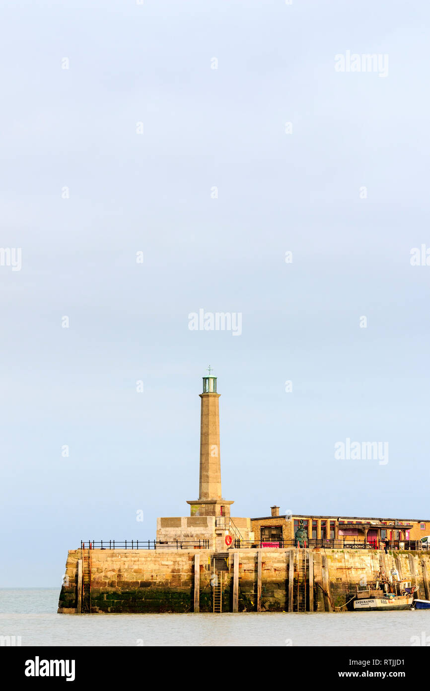 Stone concerte lighthouse on end of Margate harbour pier. Tide in, fishing boat moored against jetty. Overcast grey sky. Negative space. - Stock Image