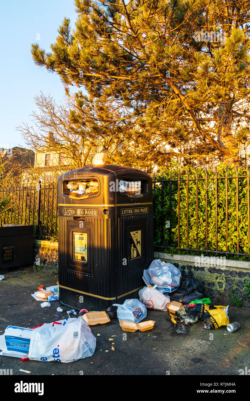 Overflowing rubbish bin on morning after a saturday night. Black large bin marked 'litter/dog waste' overflowing with tins and plastic food containers - Stock Image