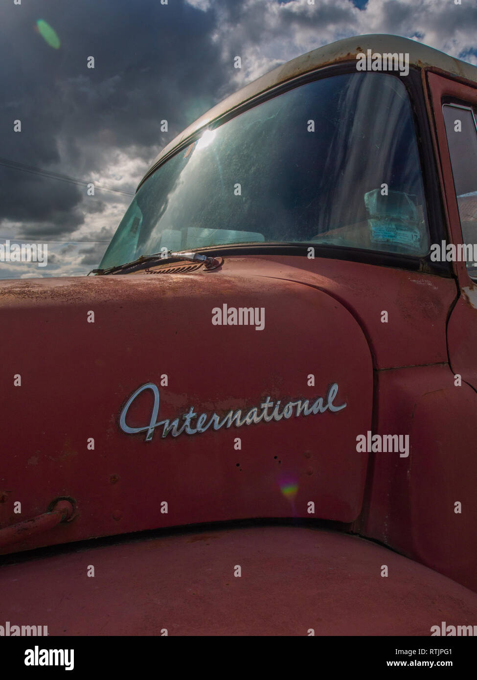 Red International truck, windscreen catching the light, curved body, Endeans Mill, Waimiha, King Country, New Zealand - Stock Image