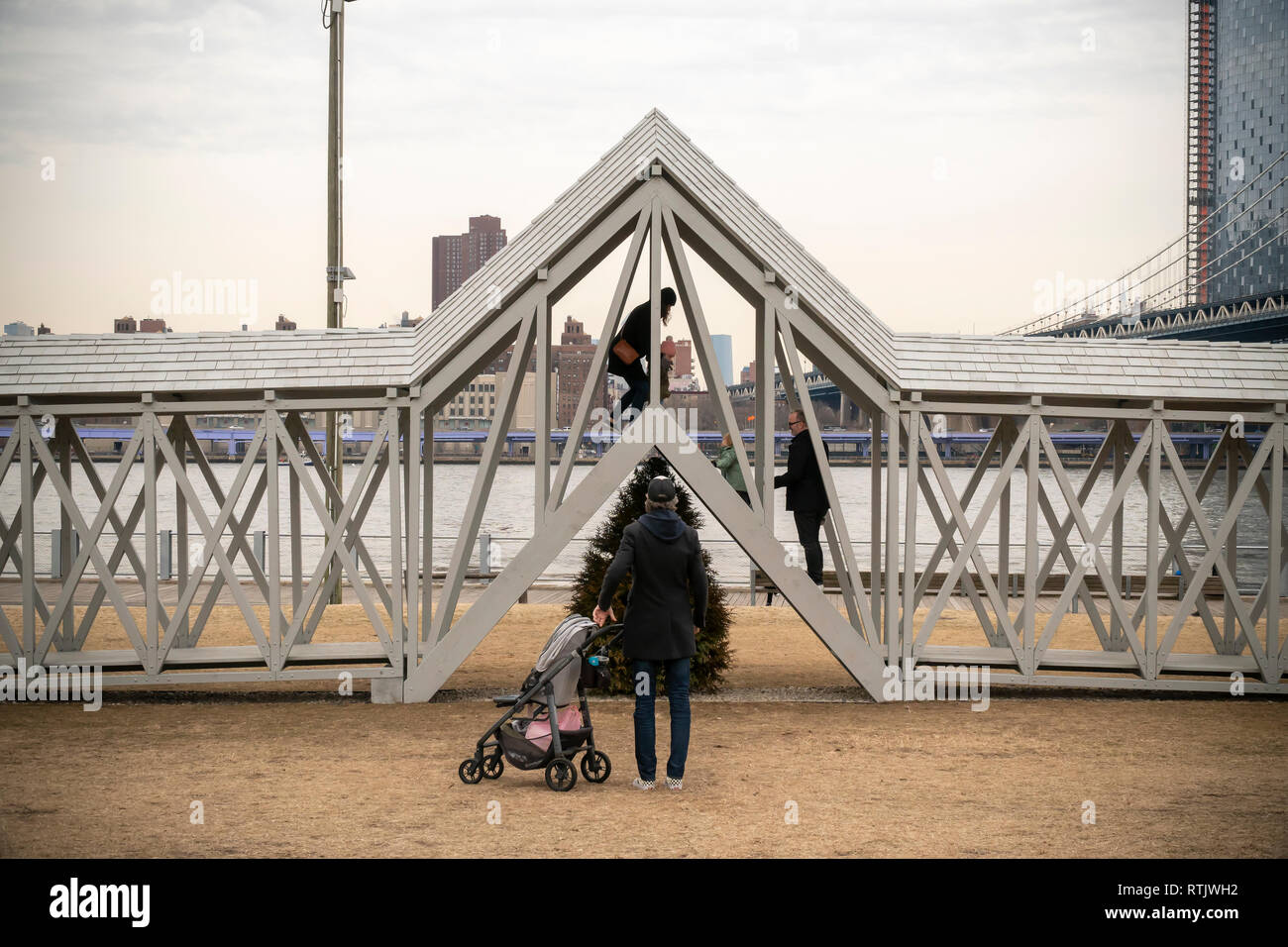Siah Armajani's experiential public art sculpture, 'Bridge Over Tree' is enjoyed by visitors to Brooklyn Bridge Park, between the Manhattan and Brooklyn bridges, in New York on Saturday, February 23, 2019. The 91-foot long piece with stairs in the center lifts the participant over a lone evergreen tree  and it is the first time the 1970 piece has been displayed in almost 50 years. The Met Breuer is hosting a retrospective of the Minneapolis based artists' works and 'Bridge Over Tree' will be on display in the park until September 29. (© Richard B. Levine) - Stock Image