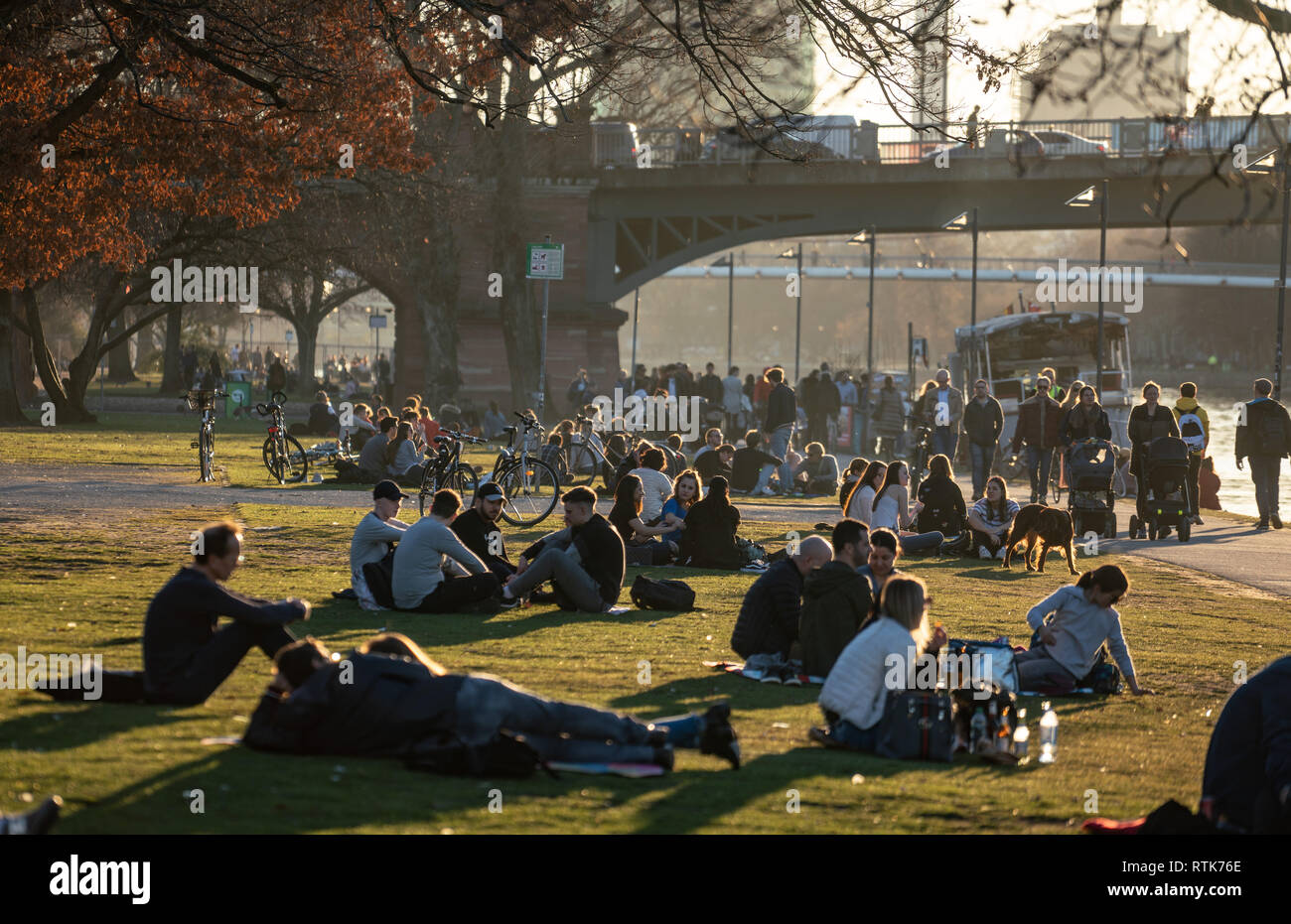 27 February 2019, Hessen, Frankfurt/Main: People cavort on the meadows and on the banks of the Main on a warm February evening. Photo: Frank Rumpenhorst/dpa - Stock Image