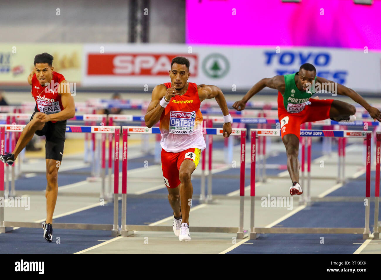 Glasgow, Scotland, UK. 2nd March, 2019. Orlando Ortega, representing Spain finishing at the men's 60 metre hurdles race at the European Athletics indoor championships, Glasgow, UK. He is pursued by Brahian Pena of Switzerland and Rasul Dabo of Portugal Credit: Findlay/Alamy Live News - Stock Image