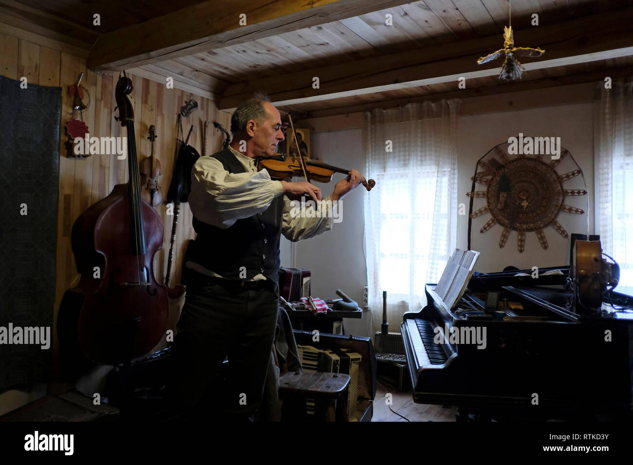 Ales Los a Belarusian ethnographer which runs Khutar Dudara (a Pipe Player's Farmstead) and is a leading restorer of ancient folk instruments, as well as a researcher of piping traditions playing the violin at his house in Volozhin District Belarus - Stock Image
