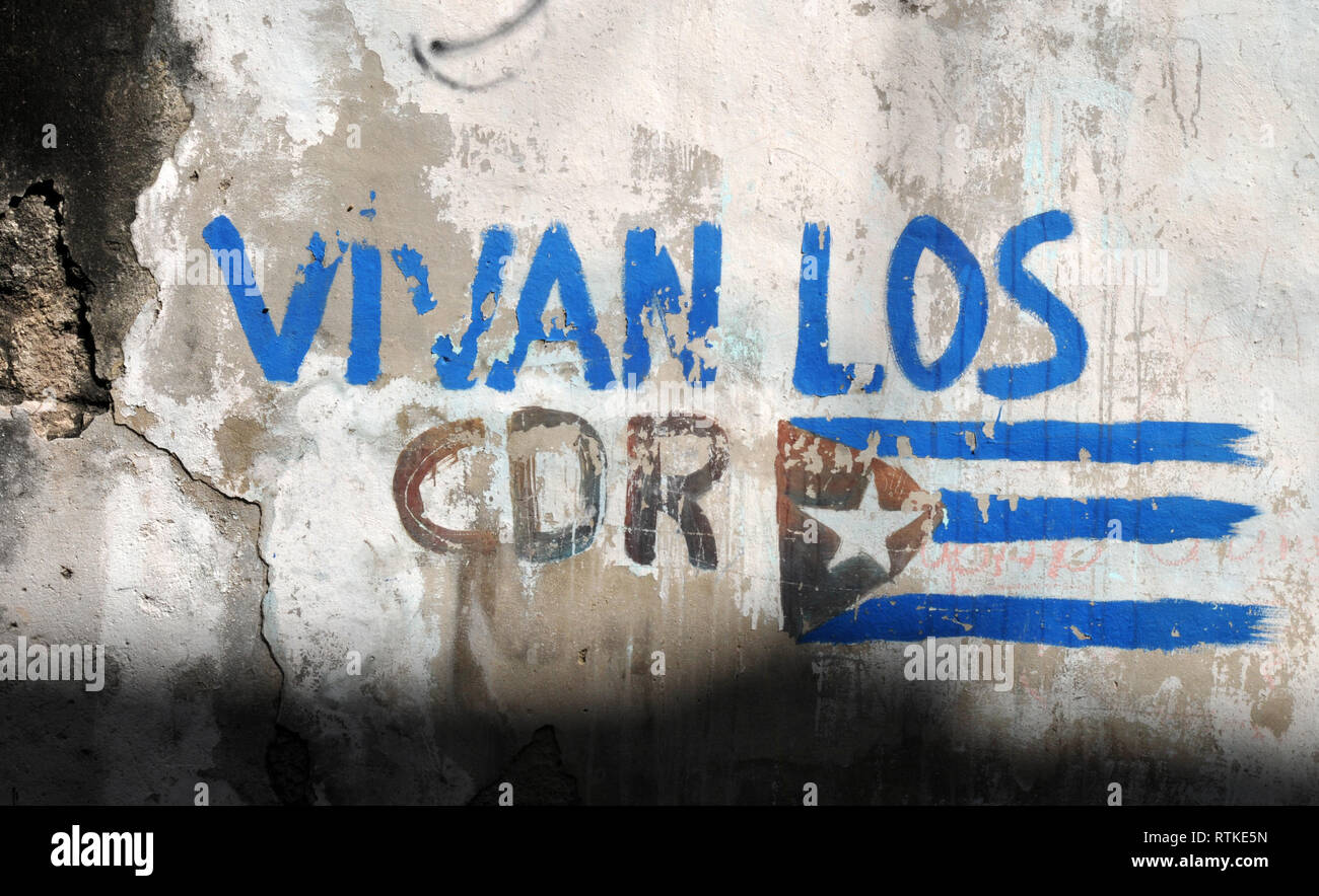 The slogan Vivan Los CDR (Long Live the Committees for the Defense of the Revolution) and a Cuban flag are painted on a building in Old Havana. - Stock Image
