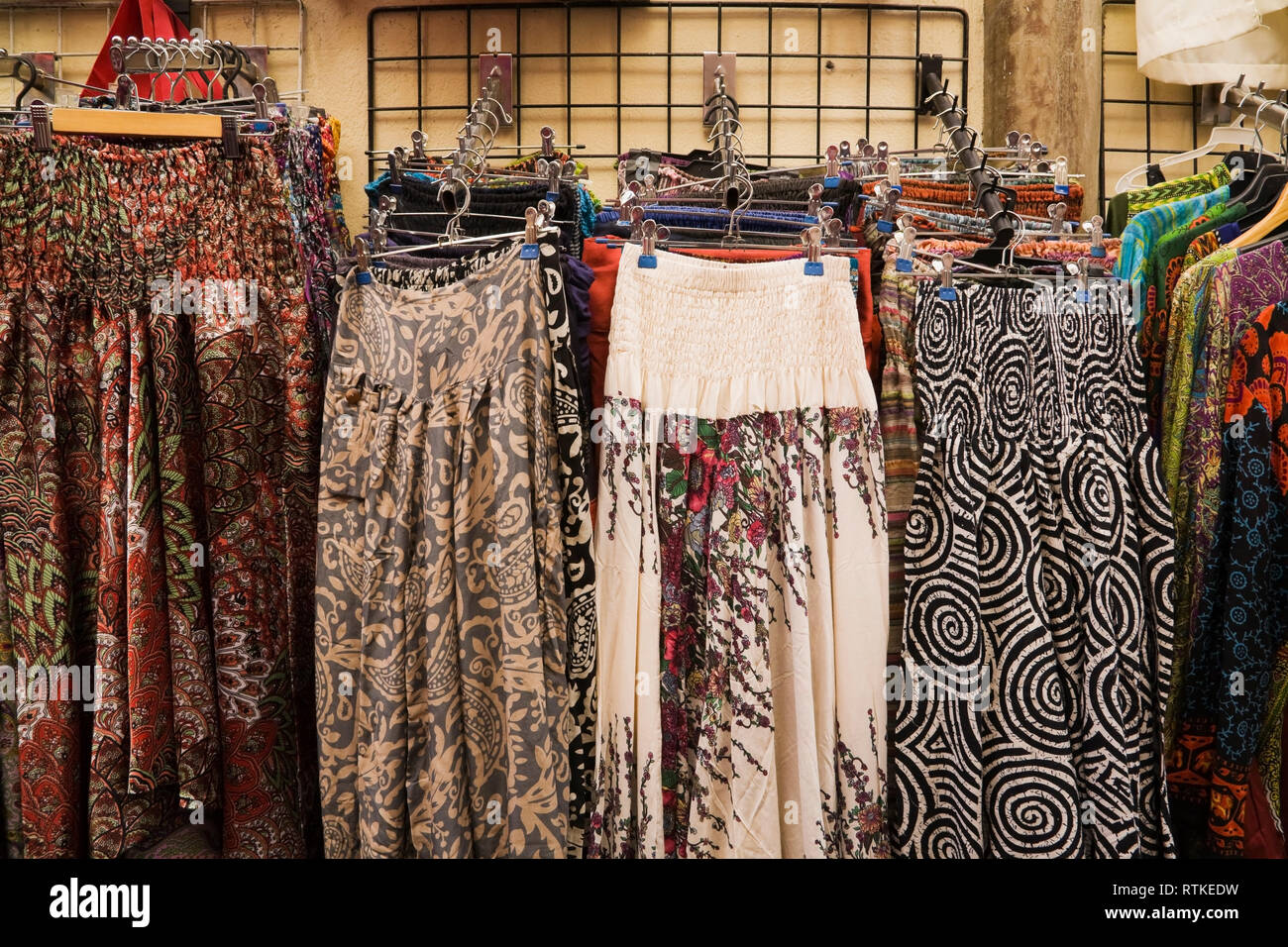 Dresses for sale in front of a shopping boutique at an Arab souk in Granada, Spain, Europe - Stock Image