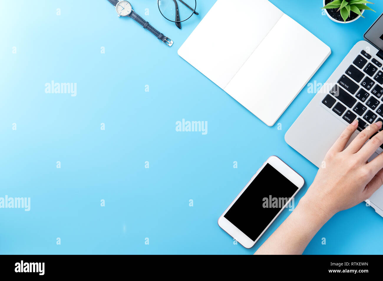 Asian student surf internet for job hunting. Freelancer blog writer typing isolated on a minimal clean blue desk concept, workspace, copy space, flat  - Stock Image