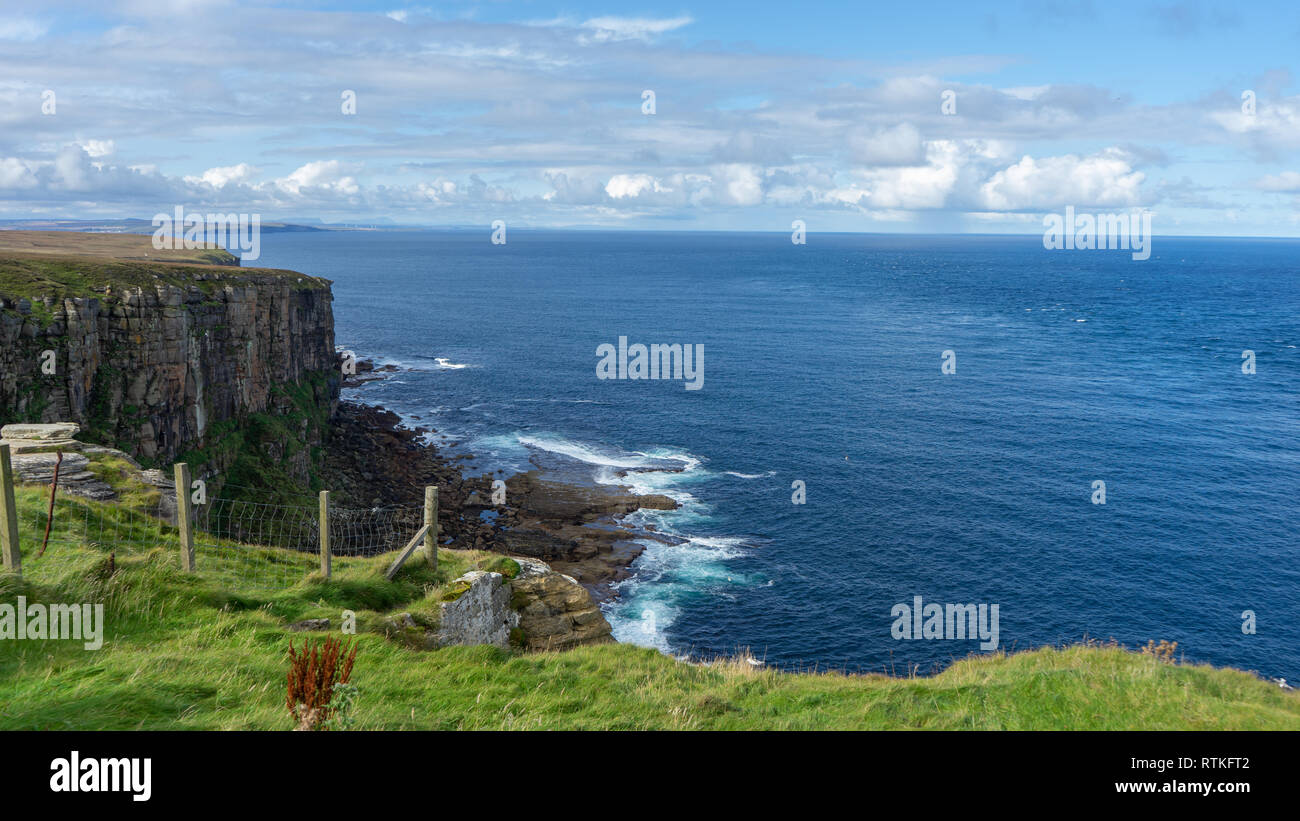 Scottish coast with view on Orkney islands and lighthouse - Stock Image