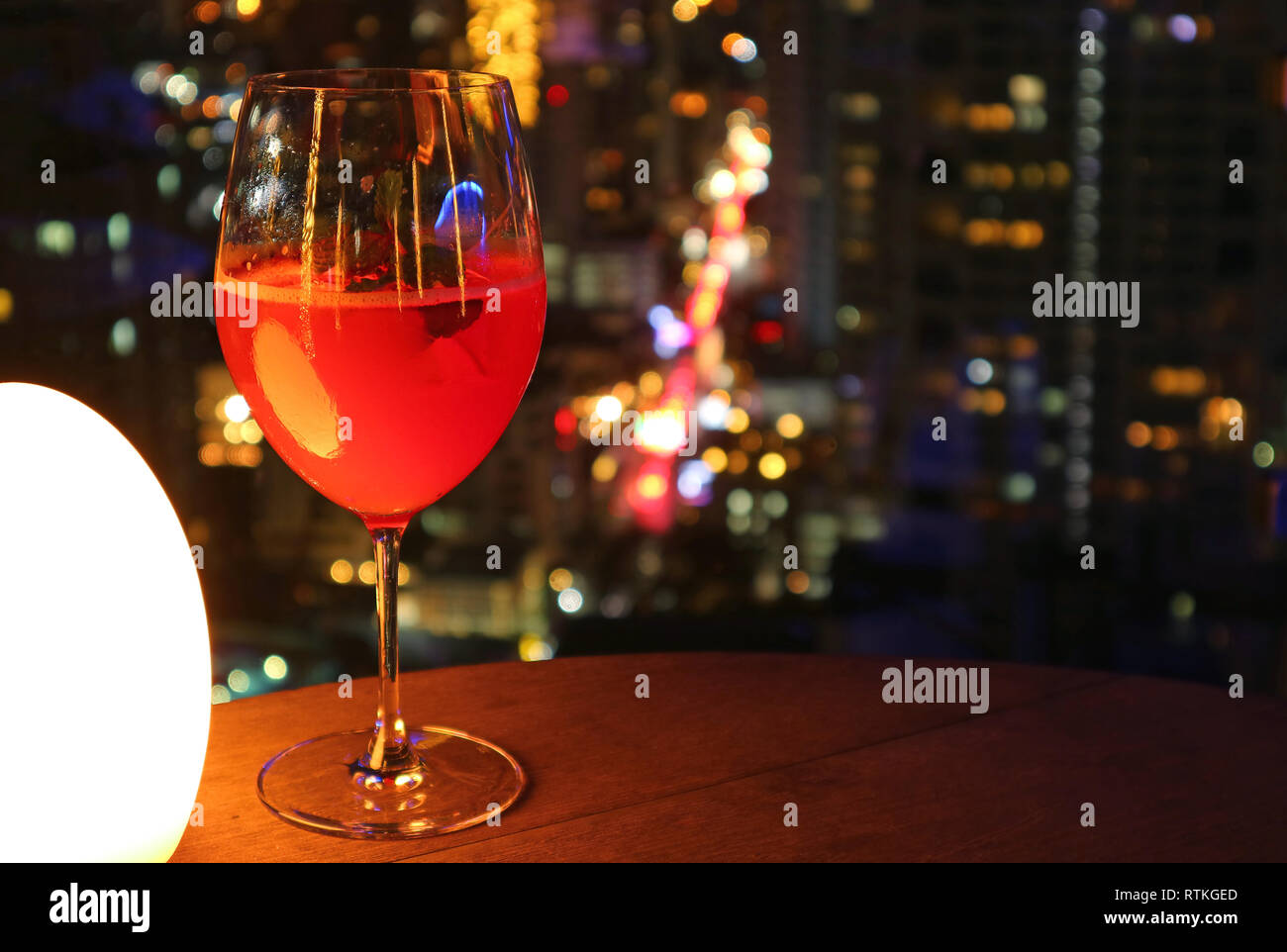 Glass of vibrant red cocktail on the rooftop bar's table with urban night view bokeh in background - Stock Image