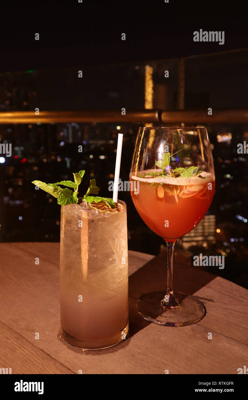 Front view of two glasses of cocktails at rooftop bar's terrace on a tropical summer night - Stock Image