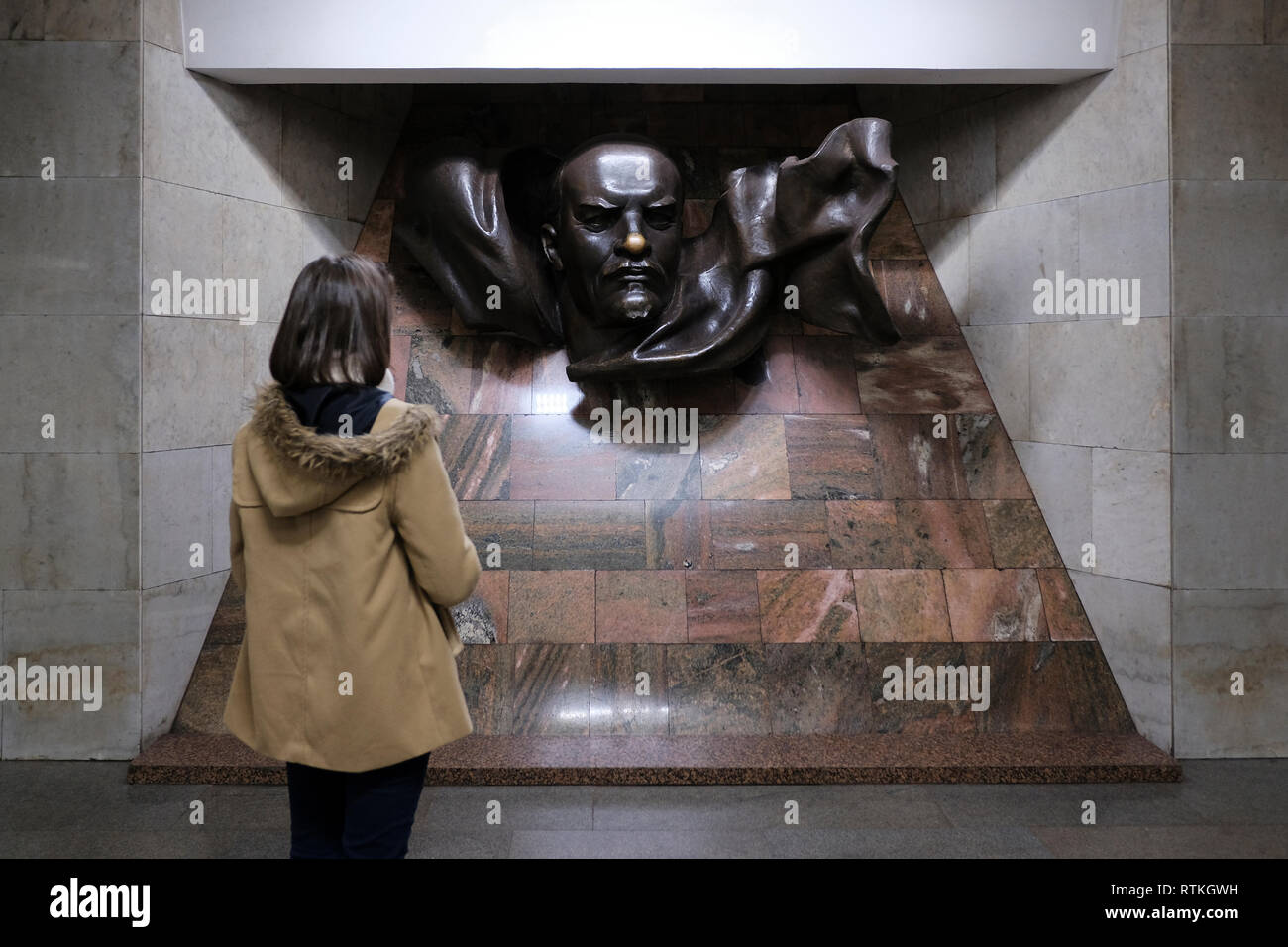A young Belarusian woman lookinf at the statue of Vladimir Lenin placed inside  Plosca Lienina (Lenin Square) Metro station in Independence Square in the city of Minsk, capital of Belarus Stock Photo