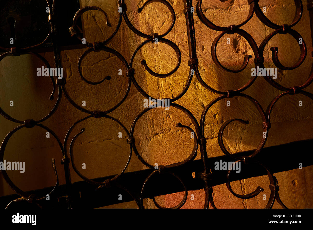 Abstract metal swirl patterns against warm stone background - Stock Image
