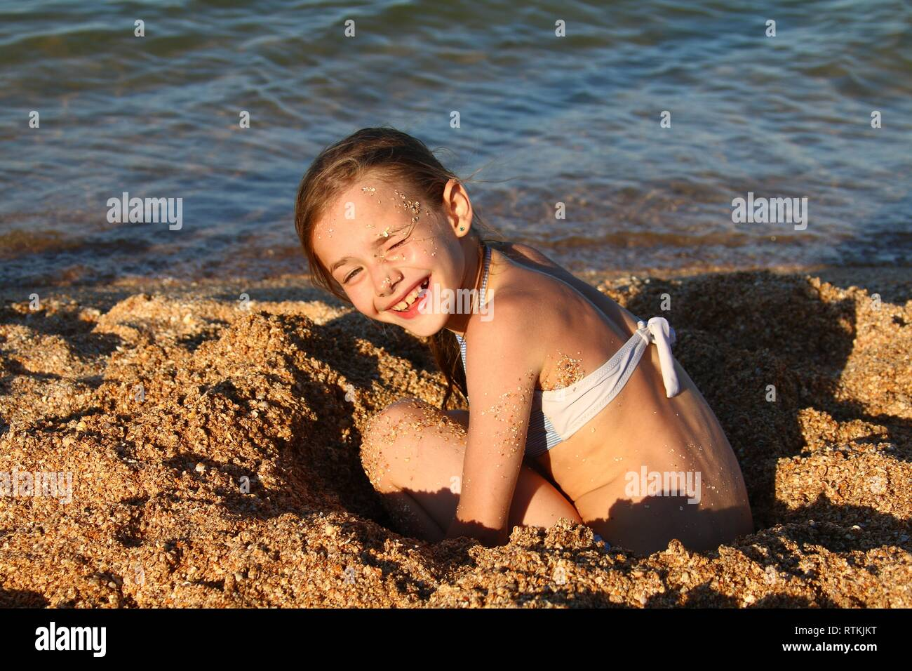 holidays, summer day on the beach by the sea, the girl happily plays with sand in the rays of the setting sun - Stock Image