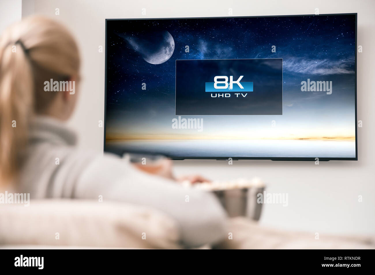 Woman watches tv with 8k ultra hd resolution. Picture on the screen created in graphic software. - Stock Image