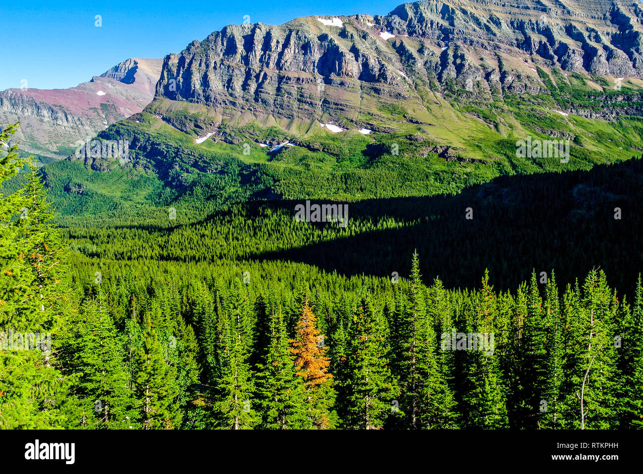 Shadows work their way across a valley in Glacier National Park - Stock Image
