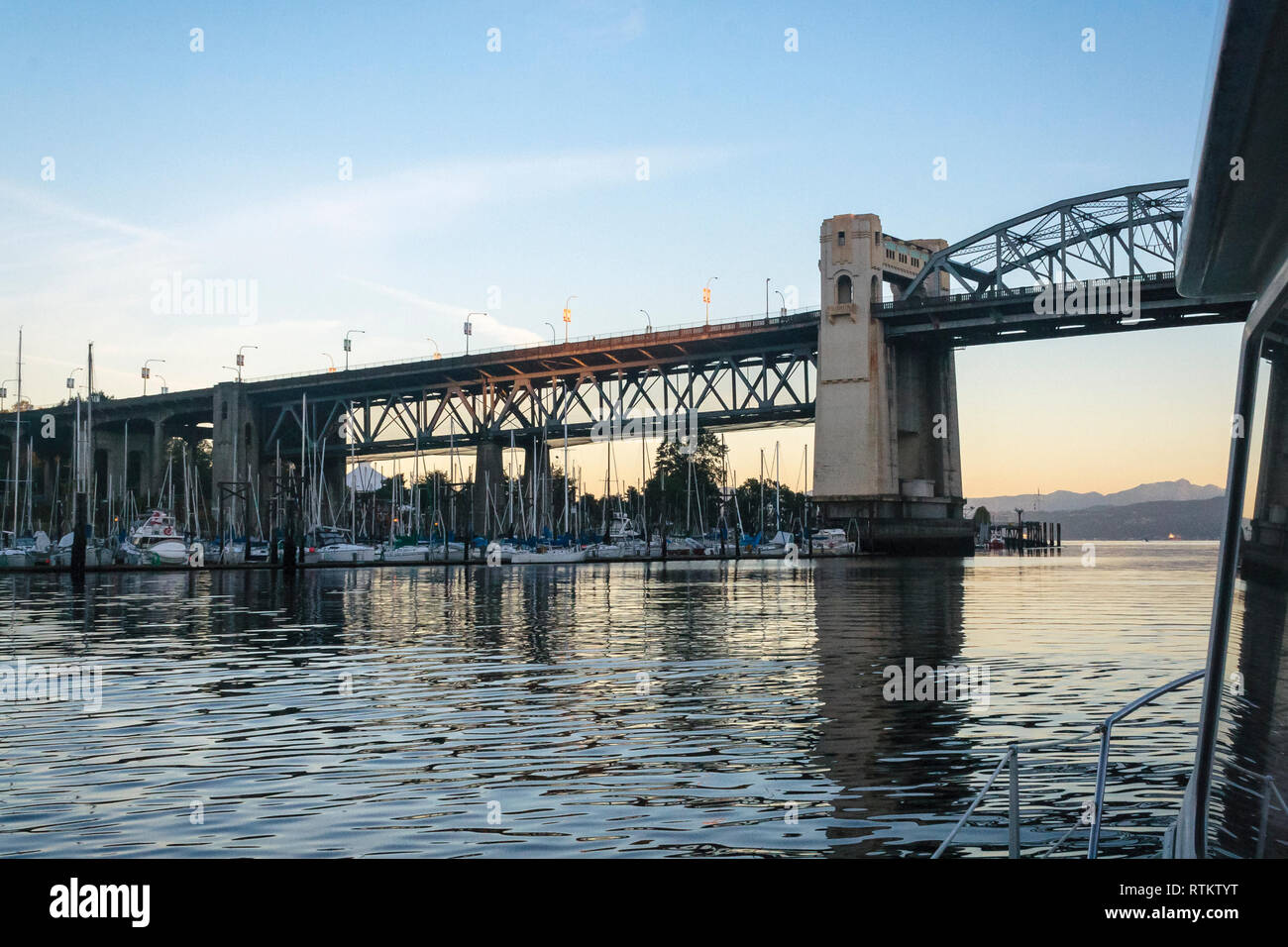 A view of False Creek and the Burrard Street Bridge at dawn, from aboard a boat about to pass under the bridge on its way out to sea from Vancouver. - Stock Image