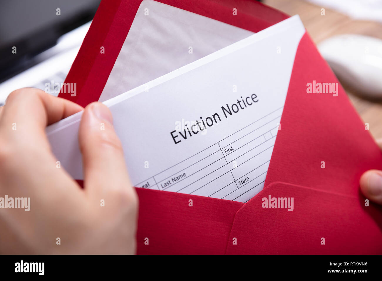 Close-up Of A Person's Hand Holding Eviction Notice In Red Envelope - Stock Image
