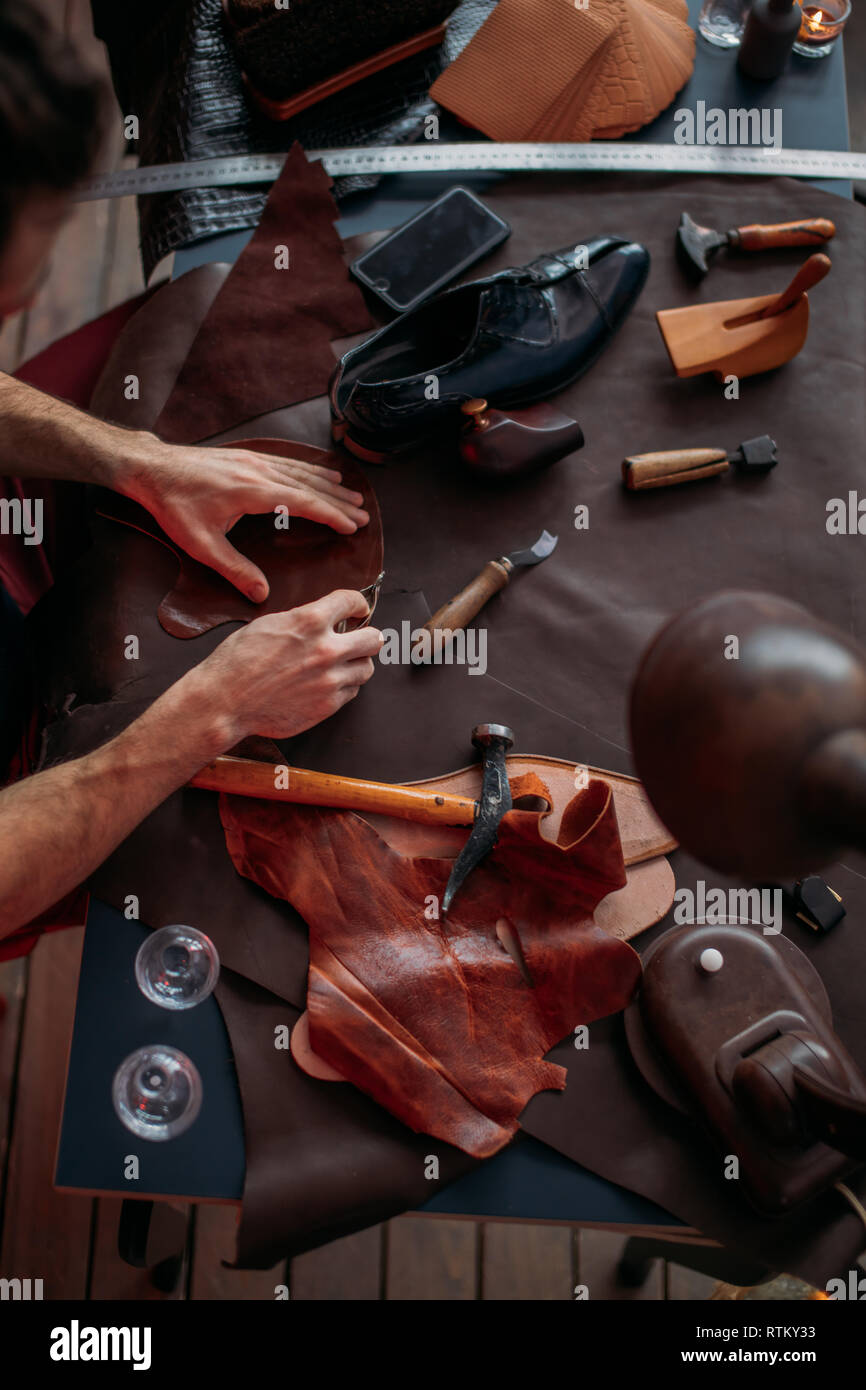 guy working with leather using crafting tool at workshop. close up cropped photo. busy working day - Stock Image
