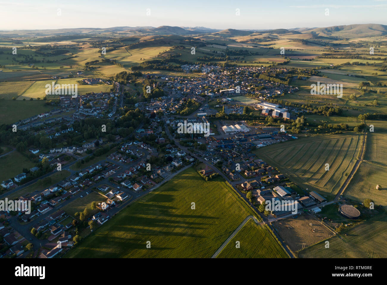 Aerial image of the town of Biggar in South Lanarkshire showing the Upper Clyde Valley and hills of the Scottish Borders Region, taken in evening sun. - Stock Image