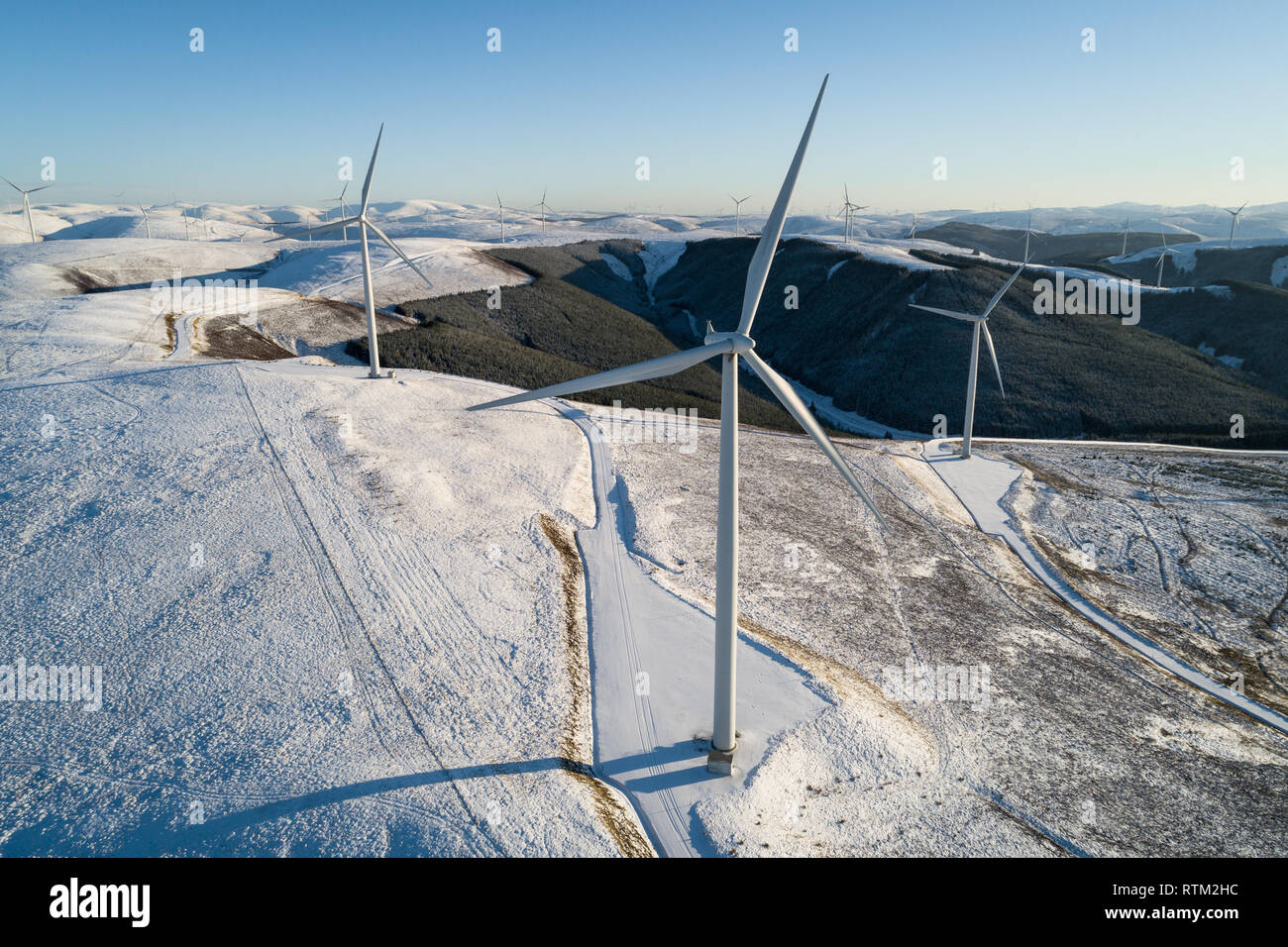 Aerial image of the Clyde Wind Farm Extension in snow on a bright winter day. The Clyde Farm is a 206 turbine 512 megawatt development in Scotland. - Stock Image