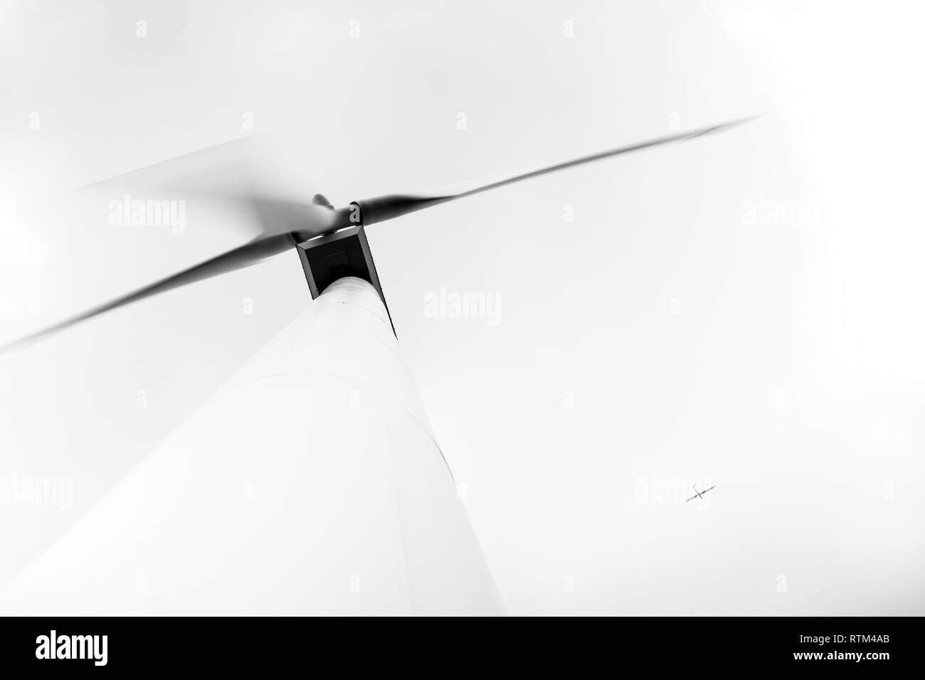 View from below of large electric environmentally friendly wind turbine with aeroplane flying high in the sky - unusual angle - Stock Image